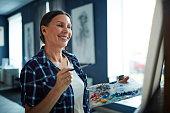 Happy elderly woman looking at her painting in art studio