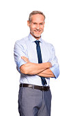 Portrait of successful mature businessman looking at camera isolated on white background. Cheerful senior business man standing with crossed arms. Smiling manager in formal isolated over white backgro
