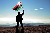 Successful silhouette man winner waving Libya flag on top of the mountain peak