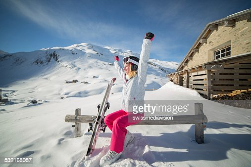 Successful skier on ski slopes near chalet-Winter