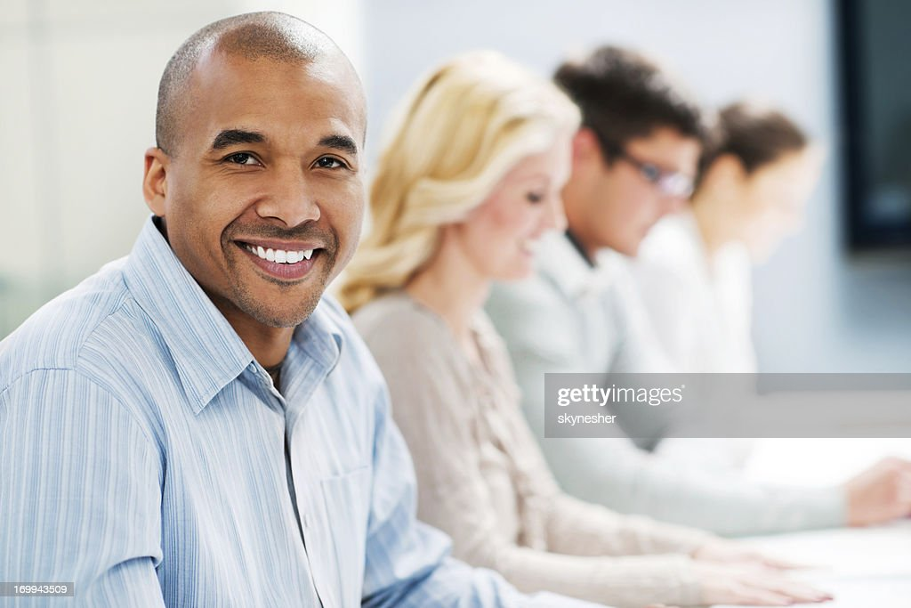 Successful smiling businessman on a meeting : Stock Photo