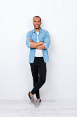 Successful smiling young handsome mulatto american student in trendy denim outfit on pure white background with crossed hands. So confident, attractive and smart