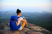 successful woman hiker reading e-book on mountain top