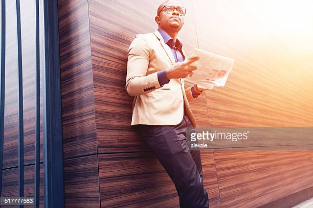 Successful young african man reading a newspaper