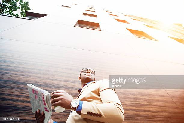 Successful young african man reading a newspaper while drinking coffee