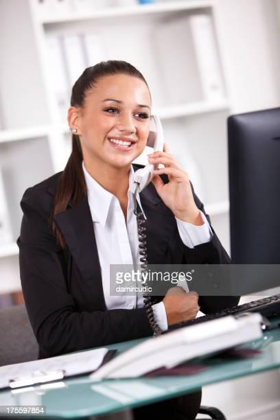 Succès jeune femme d'affaires avec ordinateur et de parler sur le téléphone