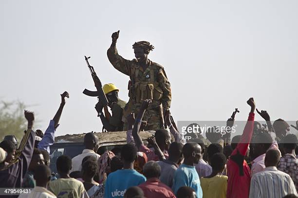A Sudan People's Liberation Army soldier waves his AK47 as soldiers celebrate alongside Internally Displaced People outside the United Nations...