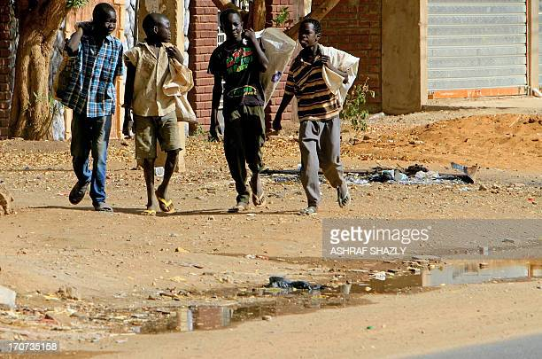 Sudanese boys arrive with bags to scour garbage in Khartoum on June 14 2013 An increasing number of Sudanese are scouring garbage to make a living in...
