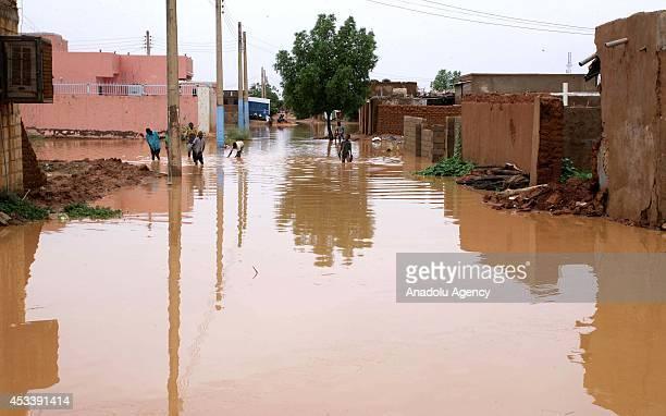 Sudanese children walk along a waterlogged street after heavy rain in Khartoum Sudan on 9 August 2014