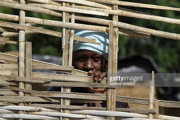 Sudanese displaced woman peeks from behind a fence on November 6 in the Kalma camp for internally displaced people located east of Nyala city in...