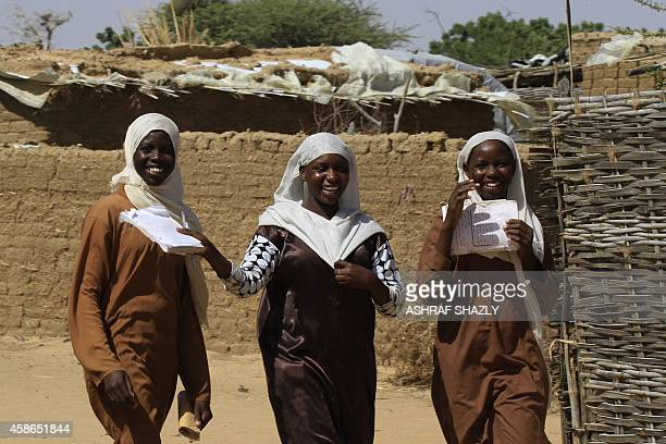 Sudanese displaced women share a laugh as they walk in the Kalma camp for internally displaced people located east of Nyala city in Sudan's Darfur on...