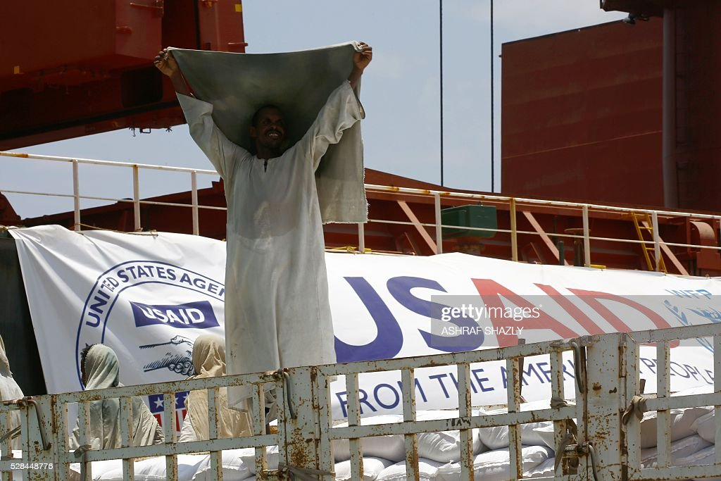 A Sudanese docker lifts his head cover as he unloads a US aid shipment organised by the US Agency for International Development and the World Food Programme at Port Sudan on the Red Sea coast, on May 5, 2016. Dockers began unloading tens of thousands of tonnes of food from a US aid ship destined for war-torn areas of Sudan, an AFP correspondent reported. The bulk carrier Liberty Grace docked in Port Sudan with a cargo of 47,500 tonnes of sorghum, a staple food in Sudan. SHAZLY