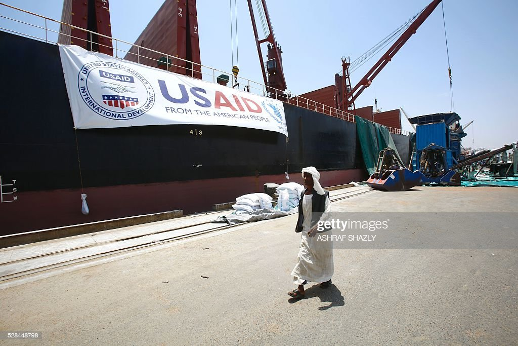 A Sudanese docker walks past a US aid shipment organised by the US Agency for International Development and the World Food Programme at Port Sudan on the Red Sea coast, on May 5, 2016. Dockers began unloading tens of thousands of tonnes of food from a US aid ship destined for war-torn areas of Sudan, an AFP correspondent reported. The bulk carrier Liberty Grace docked in Port Sudan with a cargo of 47,500 tonnes of sorghum, a staple food in Sudan. SHAZLY