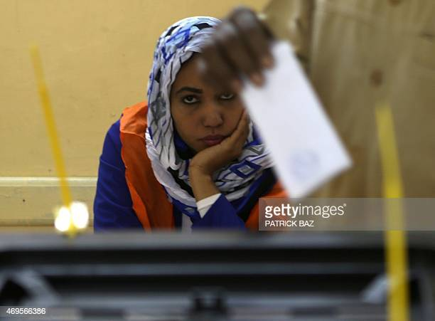 A Sudanese electoral officer looks at a man casting his vote at a polling station in Khartoum on April 13 2015 AFP PHOTO / PATRICK BAZ