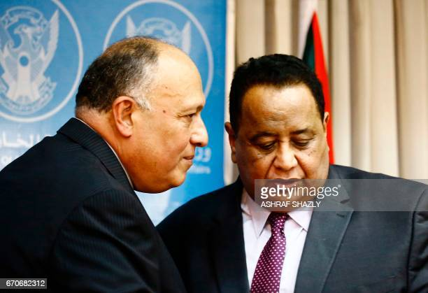 Sudanese Foreign Minister Ibrahim Ghandour speaks with his Egyptian counterpart Sameh Shokry following a press conference in Khartoum on April 20...