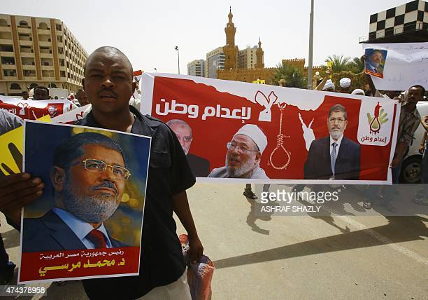 Sudanese Islamists hold posters bearing portraits of Egypt's ousted president Mohamed Morsi Egyptian Muslim Brotherhood leader Mohamed Badie and...