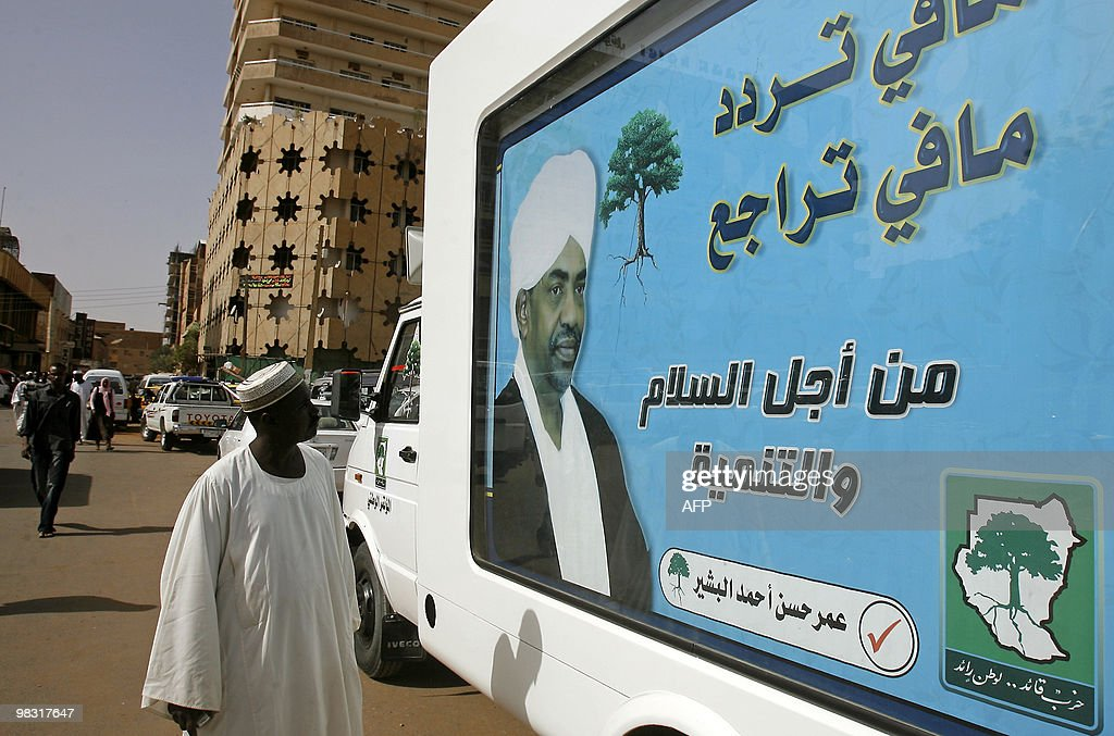 Sudanese man looks at a campaign poster for President Omar alBeshir reading in Arabic 'No hesitation no retreat For peace and development' in central...
