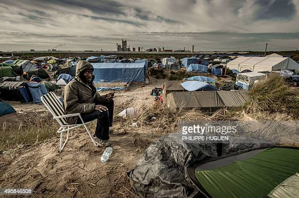 A Sudanese man looks on as he uses a phone to call his family in Sudan on November 5 2015 in the 'Jungle' migrants camp in Calais A French court on...
