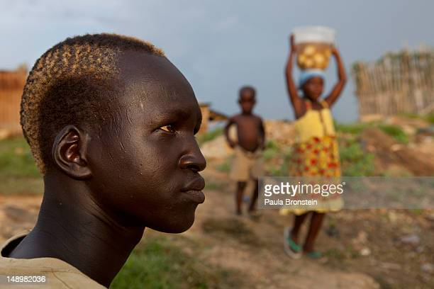 Sudanese man sits outside his home as children carry food to cook on July 20 2012 in Juba South Sudan After breaking away from Sudan last year South...