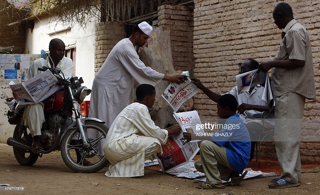 Sudanese men gather around a newspaper street vendor in a street in AlJarif city outside the capital Khartoum on May 25 2015 Sudanese security forces...