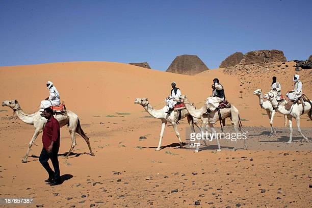 Sudanese men ride camels on November 10 2013 past pyramids in the cemetary of Meroe north of Khartoum Sudan The Meroe dynasty the last in a line of...