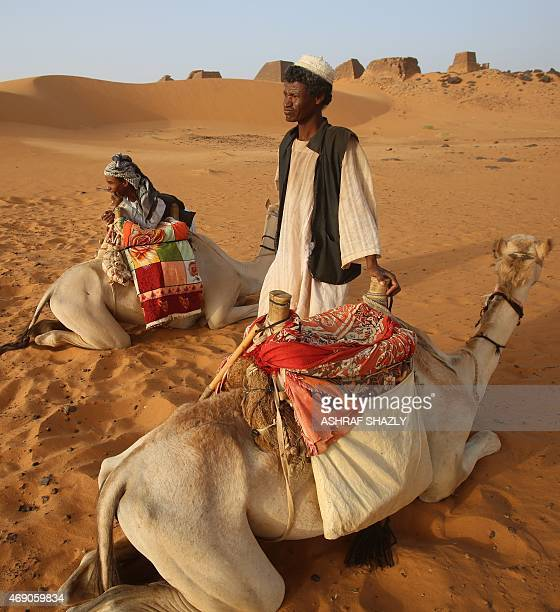 Sudanese men sit with their camels near ancient pyramids in the area of Bejrawiya near the hometown of Sudanese President Omar alBashir on April 1...
