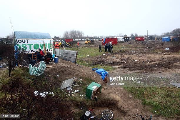 Sudanese migrants sit next to a hut marked for demolition as land is cleared around them in the 'jungle' migrant camp on March 01 2016 in Calais...