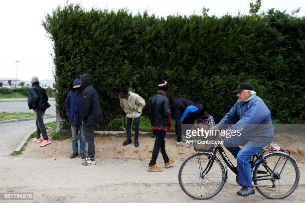 Sudanese migrants wait on the side of a road as a man on a bike passes in Ouistreham near Caen northwestern France on October 5 2017 Migration is a...
