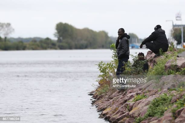 Sudanese migrants wait on the side of a road in Ouistreham near Caen northwestern France on October 5 2017 Migration is a hot button issue in Europe...