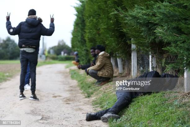 Sudanese migrants wait or sleep on the side of a road in Ouistreham near Caen northwestern France on October 5 2017 Migration is a hot button issue...