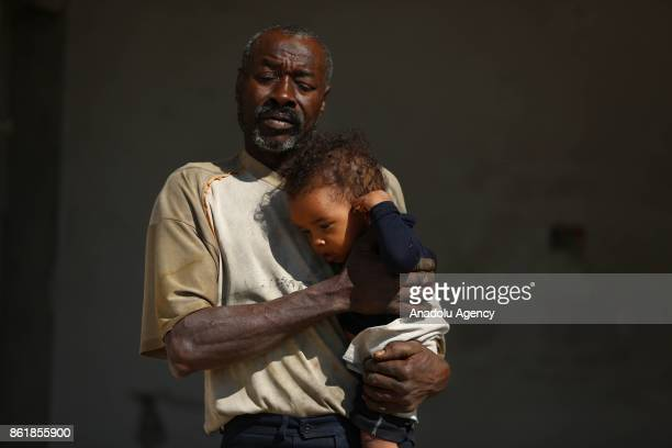 Sudanese Mirsal Ali is seen with his baby at oneroomed flat in Eastern Ghouta district of Damascus Syria on September 20 2017 Mirsal Ali hopes to...