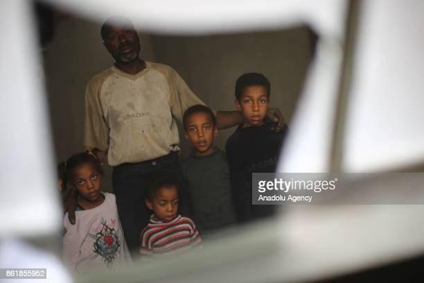 Sudanese Mirsal Ali is seen with his children at oneroomed flat in Eastern Ghouta district of Damascus Syria on September 20 2017 Mirsal Ali hopes to...
