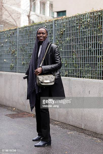 Sudanese model Grace Bol exits the Bottega Veneta show with a scarf over her head a long black leather jacket black trousers dark blue boots and a...