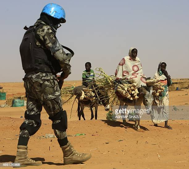 Sudanese people walk past a member of the UNAfrican Union mission in Darfur at the Zam Zam camp for Internally Displaced People North Darfur on April...