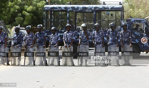 Sudanese police stand guard as hundreds of Sudanese Islamists demonstrate outside a United Nations office in central Khartoum on May 22 to protest...