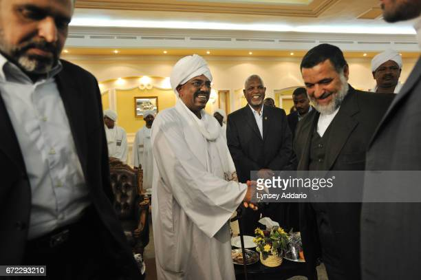 Sudanese President Al Bashir greets members of a high level delegation of Arab and Iranians including Iranian Speaker of Parliment Ali Larijani along...
