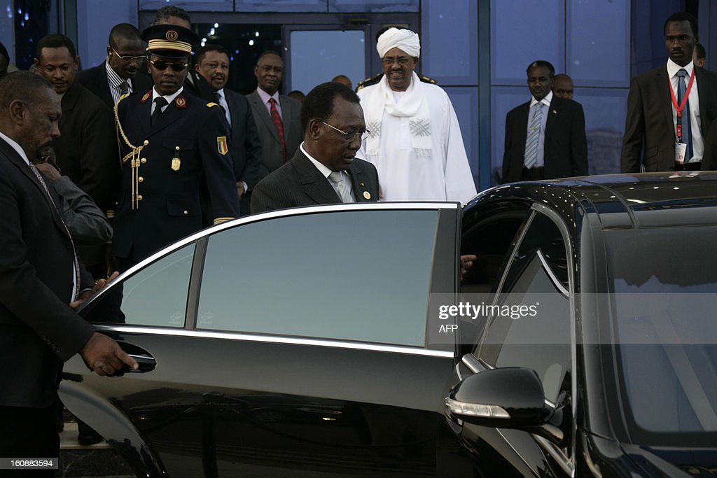 Sudanese President Omar al-Bashir (background) looks at his Chadian counterpart Idriss Deby (front) getting in a car as they leave the airport on February 7, 2013 in Khartoum.