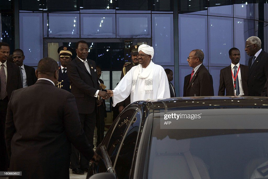 Sudanese President Omar al-Bashir (C) poses shaking hands with his Chadian counterpart Idriss Deby (2ndL) as they leave the airport on February 7, 2013 in Khartoum.