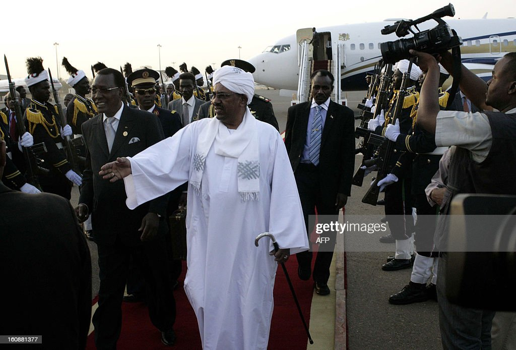 Sudanese President Omar al-Bashir (C) welcomes his Chadian counterpart Idriss Deby (L) upon his arrival at the Khartoum airport for an official visit to Sudan on February 7, 2013.