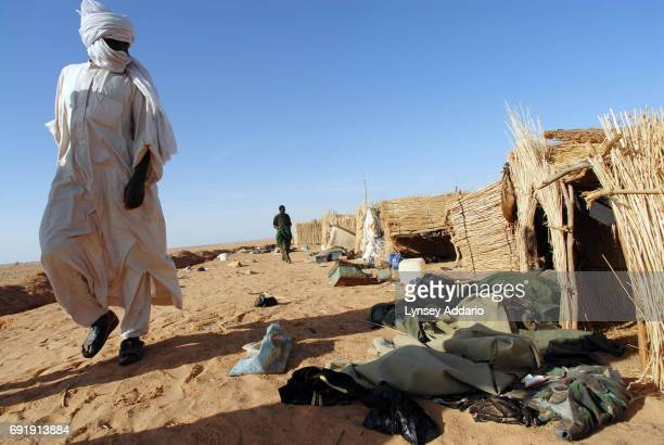 Sudanese rebels with the NRF look for ammunition and weapons and other belongings left behind from defeated GOS soldiers as the rebels walk through a...