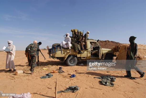 Sudanese rebels with the NRF pick up ammunition and weapons left behind from defeated GOS soldiers as the rebels walk through a temporary military...