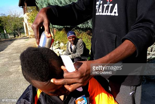Sudanese refugee cuts the hair of another outside the 'Centre dAccueil et dOrientation pour migrants' in Bruniquel near Montauban southern France on...