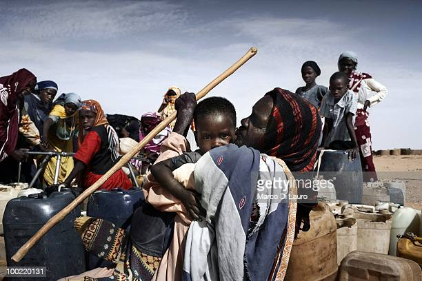 Sudanese refugees collect water at a water pump on June 20 2009 in Oure Cassoni refugee camp in Bahai Chad Since 2004 over 260000 Sudanese refugees...