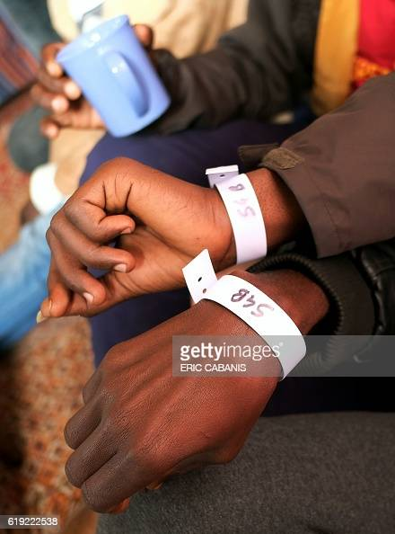 Sudanese refugees show plastic bracelets indicating a bus number in the 'Centre dAccueil et dOrientation pour migrants' in Bruniquel near Montauban...