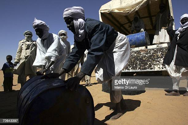 Sudanese refugees unload from a track petrol for cooking at a local health center in the Oure Cassoni Refugee Camp November 24 2006 in Bahai Chad...