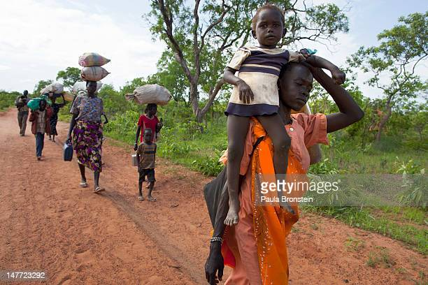 Sudanese refugees walk along the border road after crossing from North Sudan carrying what they can on July 2 2012 in Jaw South Sudan The Yida...