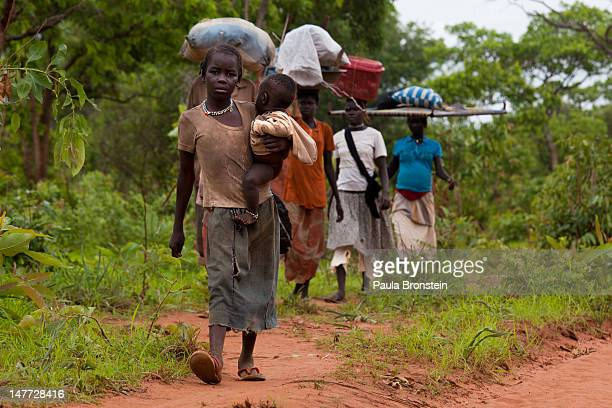 Sudanese refugees walk along the border road after crossing from North Sudan carrying their possessions July 2 2012 in Jaw South Sudan Many refugees...