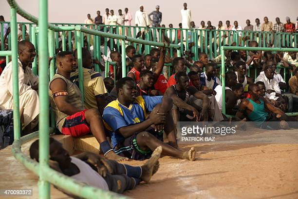 Sudanese spectators and Nubian wrestlers attend a Nubian wrestling tournament in Khartoum on April 17 2015 Nuba wrestling is a tradition in the Nuba...