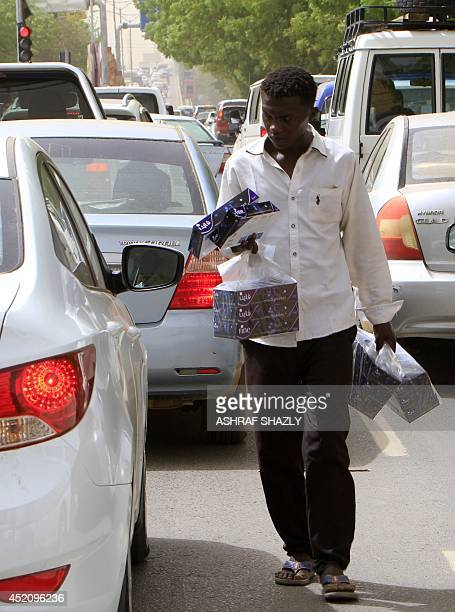 Sudanese street vendor sells boxes of tissues to motorists stuck in gridlock on one of central Khartoum's busiest road on July 13 2014 in the...