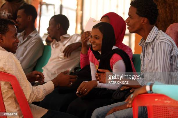 Sudanese students chat at the campus of AlNeelain University in Khartoum on April 18 2010 Opposition campaign posters are sidelined by those in...